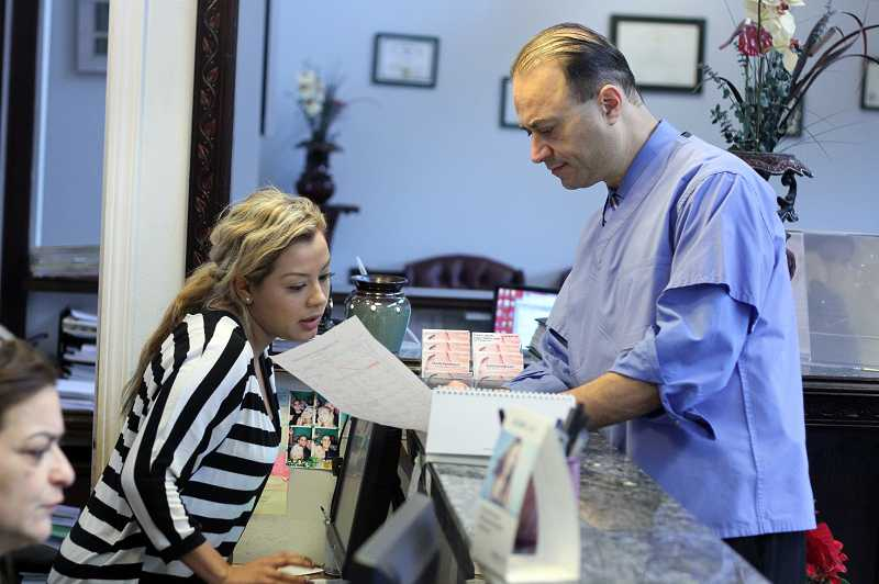 by: TIMES PHOTO: JONATHAN HOUSE - Arab American Cultural Center of Oregon President Hadi Nouredine goes over a patient schedule at his dentistry office with assistant Christine Carrillo.