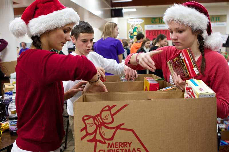 by: TIMES PHOTO: JAIME VALDEZ - Jesuit juniors Emily Hodges, left, David Ganz and Jessica Bramlett fill a box with food for a needy family during their schools 44th annual food drive.