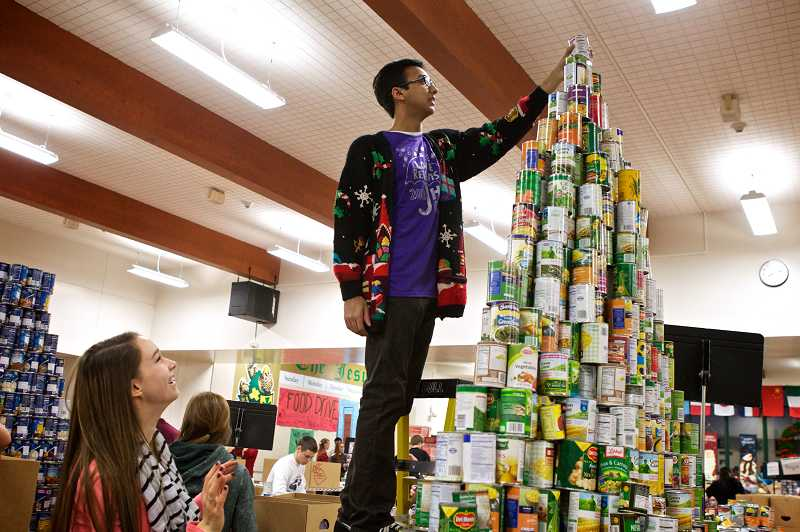 by: TIMES PHOTO: JAIME VALDEZ - Maddy Sandquist watches as Favian Rahman removes a can from atop a pyramid of canned goods to be put in a box for a needy family during their schools 44th annual food drive.