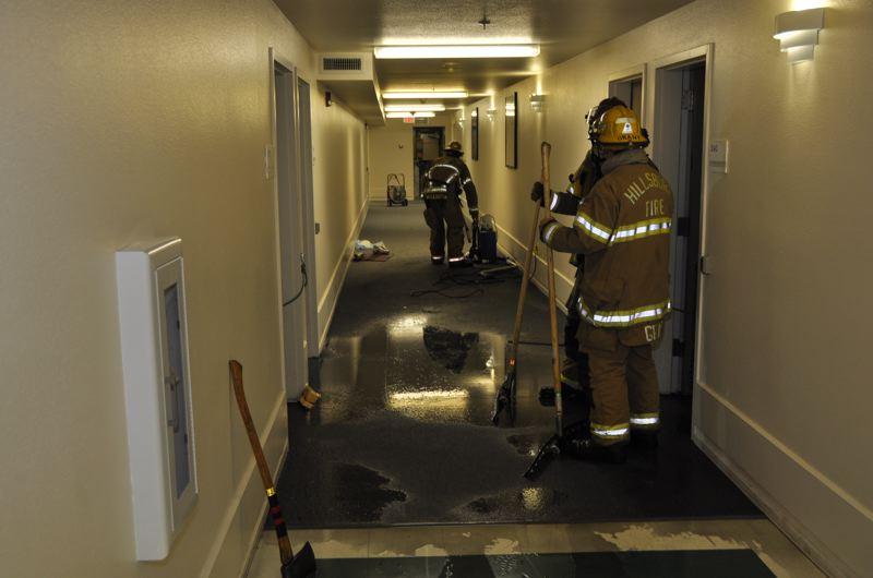 by: HILLSBORO FIRE AND RESCUE - Firefighters clean up water from the Rolling Green Apartments after the fire is extinguished.