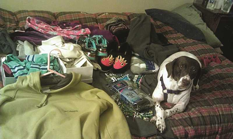 by: SUBMITTED PHOTO - At Good Neighbor Center shelter in Tigard, the Lamothe family's companion animal, Crissy, lays next to donated clothes and gifts the family of four received from the community for Christmas. The Lamothes have been staying at Good Neighbor for six weeks.