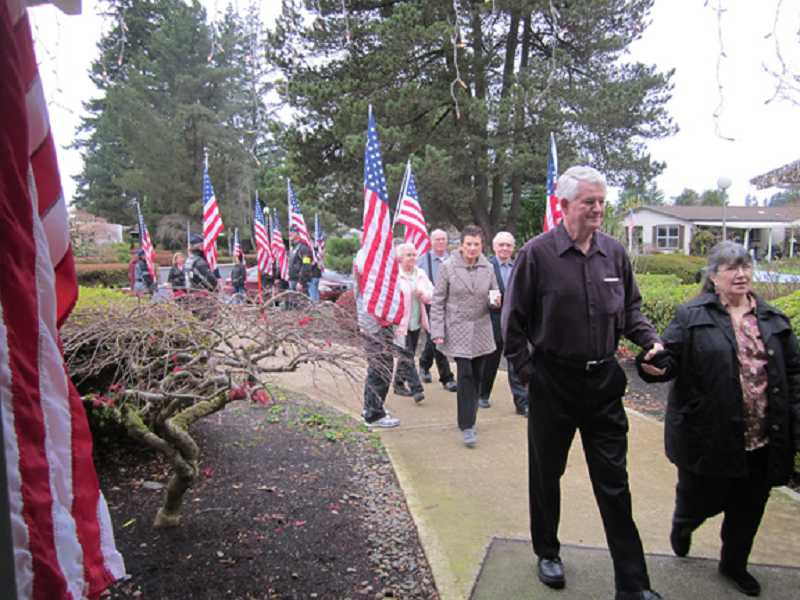 by: BARBARA SHERMAN - SHOW OF SUPPORT - Friends of Keith DeLashmutt walk between lines of Patriot Guard Riders holding flags outside the Royal Villas Clubhouse.