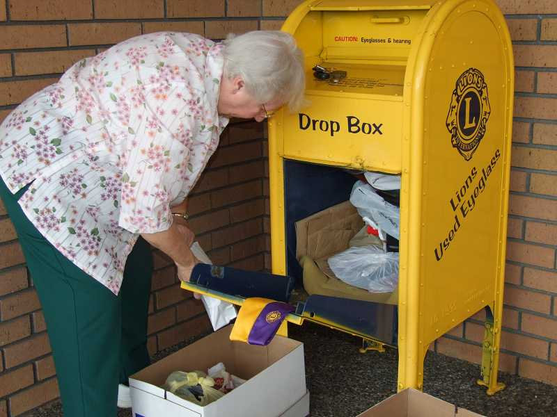 by: LAWRENCE TORREY - MISSION OF MERCY - Mary Thibert is the King City Lions Club official collector of eyeglasses, and here she empties a drop box in front of McCann's Pharmacy & Gifts.
