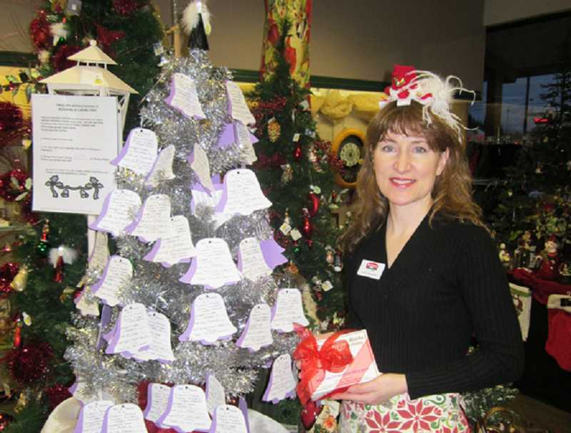 by: BARBARA SHERMAN - WISHES COME TRUE - Lu Ann Trotebas, McCann's gift buyer/manager, stands by the giving tree full of gift certificate requests from Twality Middle School students.