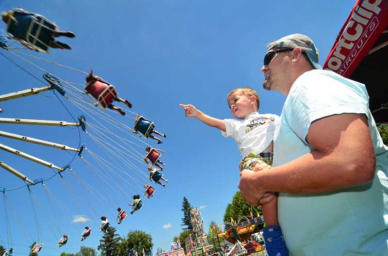 West Linn's Dylan Baltz, 2, watches his sibling on one of the carnival rides at last July's Old Time Fair at Willamette Park.