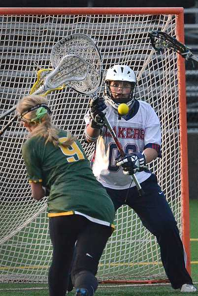 Lake Oswego girls lacrosse goalie prepares for a shot from West Linn's Kayla Bouchard in the state title game.