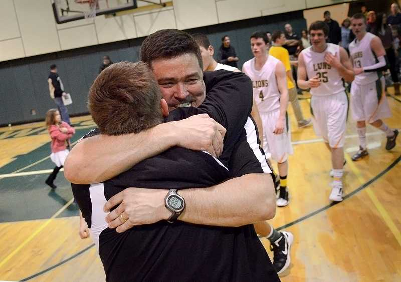 West Linn head boys basketball coach Erix Viuhkola, right, and Principal Lou Bailey celebrate after the Lions defeated Century High School to advance to the state quarterfinals at the Rose Garden back in March.