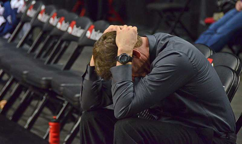 Lake Oswego High School boys basketball coach Mark Shoff sits after losing to Jesuit in the Championship game.