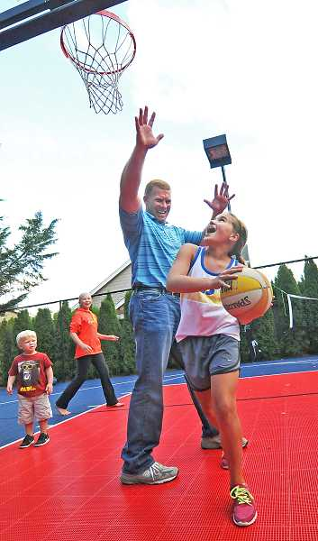 by: VERN UYETAKE - Ryan Holmes plays basketball with his kids and a neighbor, Brook Pene, on the sport court at his home on Kensington Drive. Neighbors have complained about the noise and the light associated with the court.