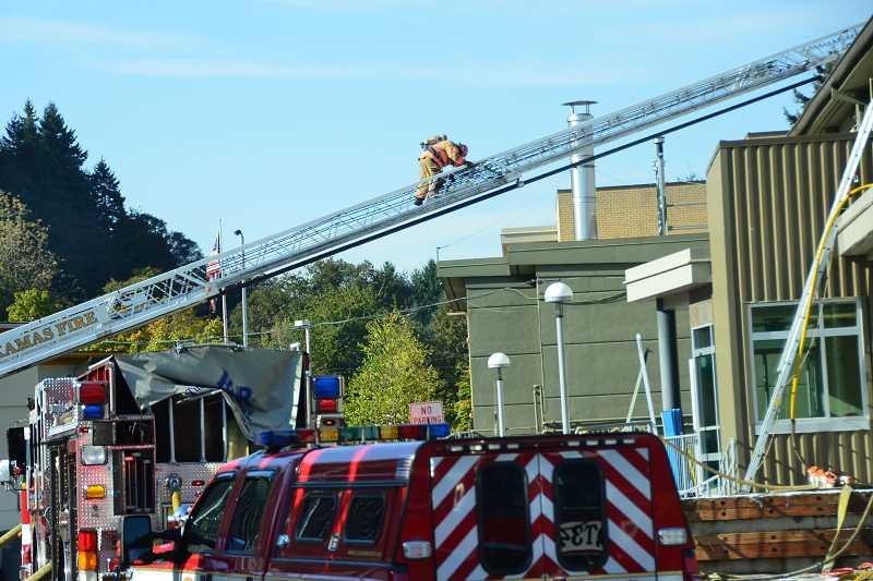 by: TIDINGS FILE PHOTO: VERN UYETAKE - Firefighters extinguish flames atop the gym at West Linn High School. The fire ignited due to sparks from a welder on Oct. 8.