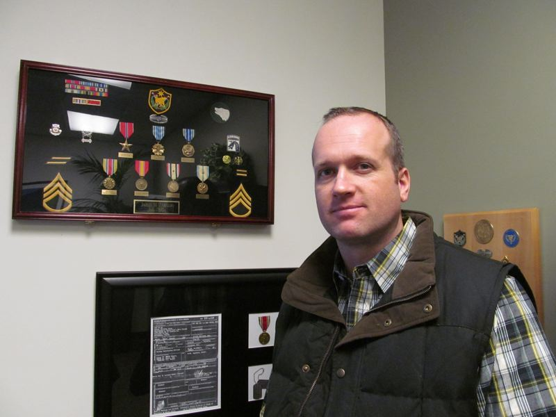 by: PHOTO BY ELLEN SPITALERI - Jared Zabaldo stands by the shadow box that was the inspiration for his company, USA Military Medals. He earned the awards as a result of a tour of duty in Iraq in 2004.