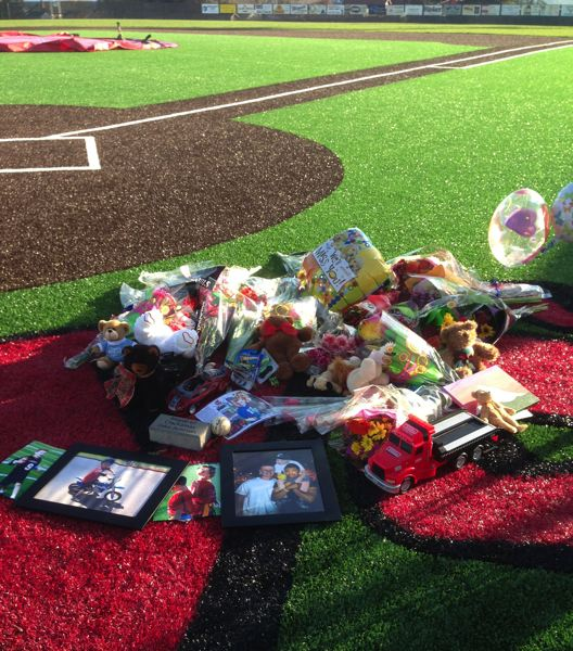 by: COURTESY: JEFF ERDMAN - Many flowers, toys and books left at a memorial on the Clackamas High School field will stay as long as weather allows.