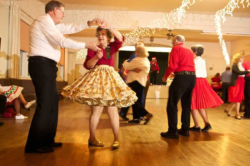 by: TIMES PHOTO: JAIME VALDEZ - Dale Brabham twirls his partner, Mary Theirl of Milwaukie, at a Tri Squares square dance in December. Square dancing comes in two varieties, teams of eight who dance in 'squares' and 'round dancing' with two dancers. In each type, dancers perform the moves as called by a caller, or cuer, who decides what dance moves should be done, and when.