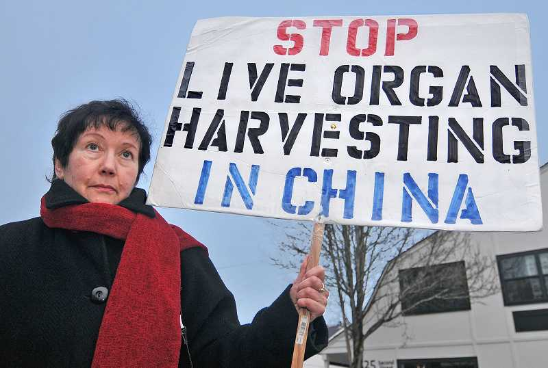 by: VERN UYETAKE - Nataly Teplitsky has a large sign and a strong voice to protest the persecution of Falun Gong members in China.