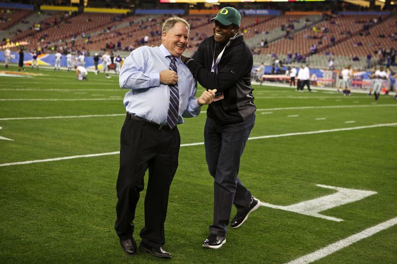 by: TRIBUNE PHOTO: JAIME VALDEZ - Former Oregon star Ahmad Rashad (right) ribs coach Chip Kelly as the Ducks go through their pregame paces at University of Phoenix Stadium.