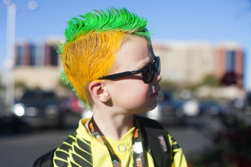 by: TRIBUNE PHOTO: MEG WILLIAMS - Riley McGarry, 6 ,of Salt Lake City wears a yellow and green mohawk before the Fiesta Bowl.