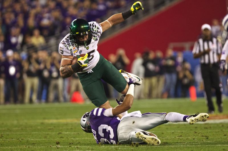 by: TRIBUNE PHOTO: JAIME VALDEZ - Oregon tight end Colt Lyerla lunges over Kansas State's Jarard Milo on the Ducks' touchdown drive late in the first half of the Fiesta Bowl.