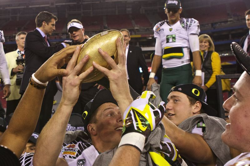 by: TRIBUNE PHOTO: JAIME VALDEZ - Oregon Ducks players hold up the Fiesta Bowl trophy after defeating the Kansas State Wildcats 35-17.
