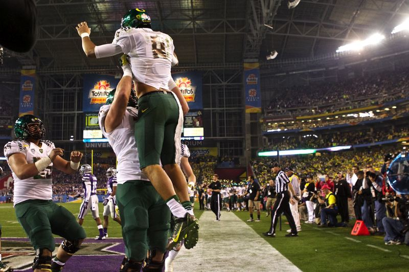 by: TRIBUNE PHOTO: JAIME VALDEZ - Oregon Ducks quarterback Marcus Mariota is hoisted by teammate Jake Fisher after Mariota scored a touchdown in the second half.