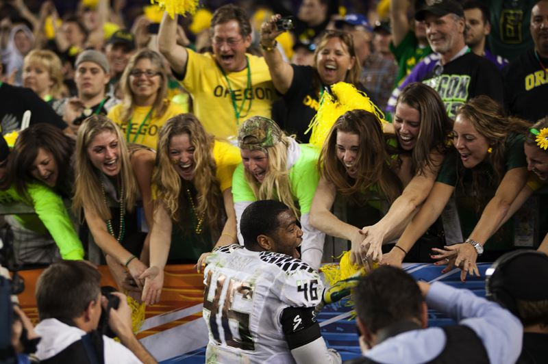 by: TRIBUNE PHOTO: MEG WILLIAMS - Oregon fans at University of Phoenix Stadium savor the 35-17 Fiesta Bowl victory over Kansas State with Oregon linebacker Michael Clay, who was named the game's top defensive player.