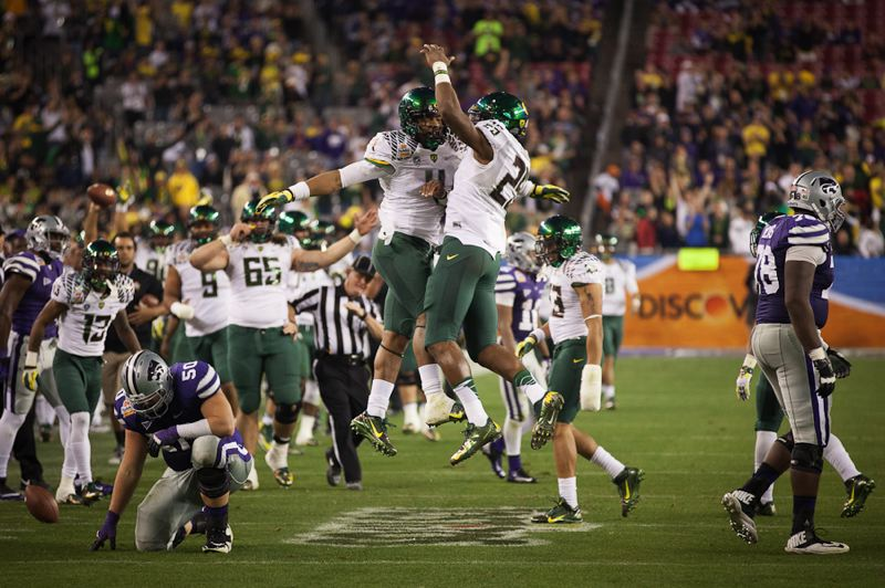by: TRIBUNE PHOTO: MEG WILLIAMS - Oregon safety Erick Dargan (4) leaps with linebacker Boseko Lokombo after making an interception in the Fiesta Bowl.