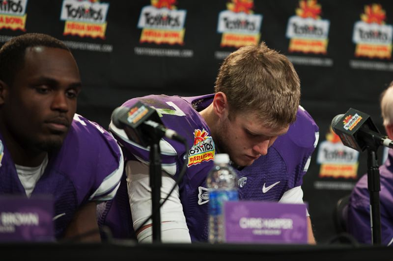 by: TRIBUNE PHOTO: MEG WILLIAMS - Kansas State quarterback Collin Klein hangs his head during the postgame press conference at the Fiesta Bowl.