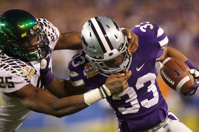 by: TRIBUNE PHOTO: JAIME VALDEZ - Oregon Ducks linebacker Boseko Lokombo tackles Kansas State running back John Hubert in the second half of the Fiesta Bowl.