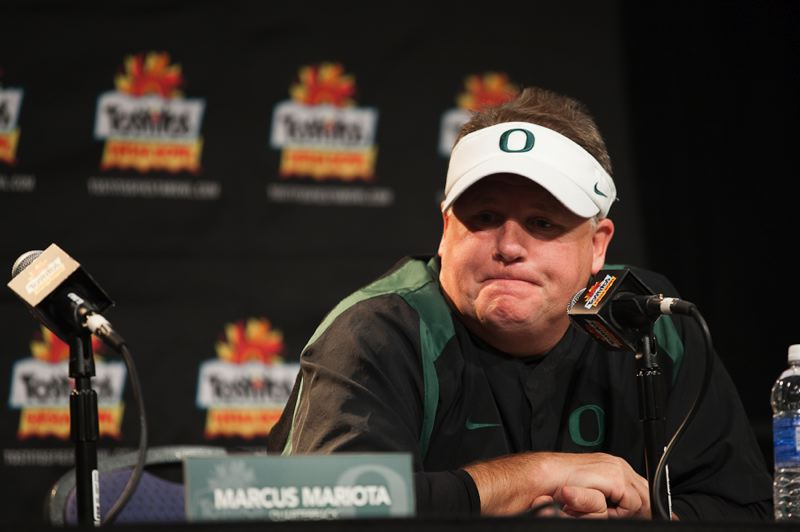 by: TRIBUNE PHOTO: MEG WILLIAMS - Oregon Ducks coach Chip Kelly listens to a question during the Fiesta Bowl postgame press conference.