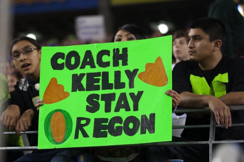 by: TRIBUNE PHOTO: MEG WILLIAMS - Oregon Ducks fans at Thursday's Fiesta Bowl show their feelings about possibly losing coach Chip Kelly to the NFL.