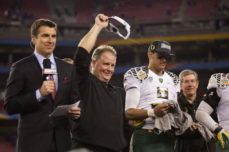 by: TRIBUNE PHOTO: MEG WILLIAMS - Oregon coach Chip Kelly doffs his visor to the crowd during the Fiesta Bowl trophy presentation on the field at University of Phoenix Stadium with ESPN's Rece Davis (left), Ducks quarterback Marcus Mariota and the rest of the winning team.