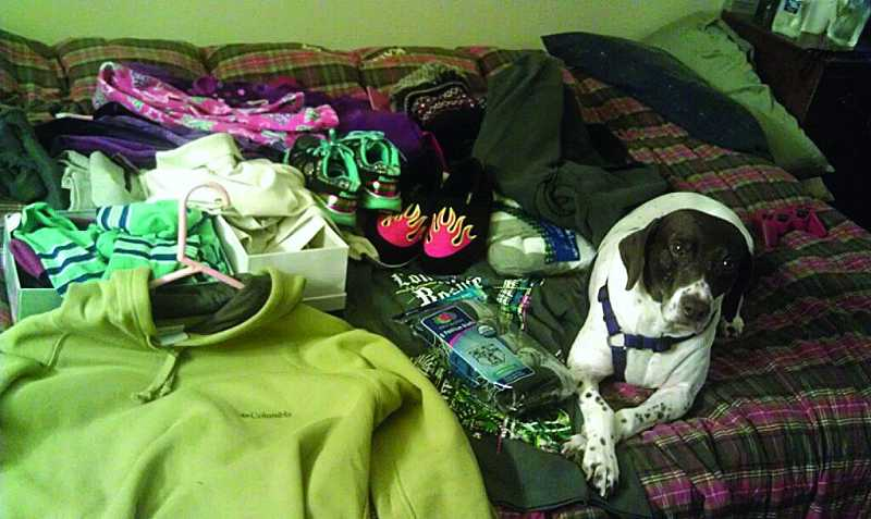 by: SUBMITTED PHOTO - At Good Neighbor Center shelter in Tigard, the Lamothe family's companion animal, Crissy, lies next to donated clothes and gifts the family of four received from the community for Christmas. The Lamothes stayed at Good Neighbor for six weeks.
