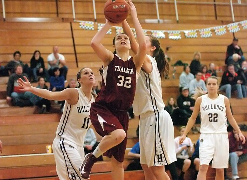 by: DAN BROOD - NICE MOVE -- Tualatin junior post Savannah Heugly (32) drives past a pair of Hermiston defenders during Saturday's tournament game.