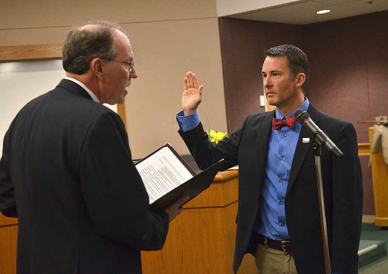by: VERN UYETAKE - Councilor Jon Gustafson takes the oath of office Tuesday at city hall.
