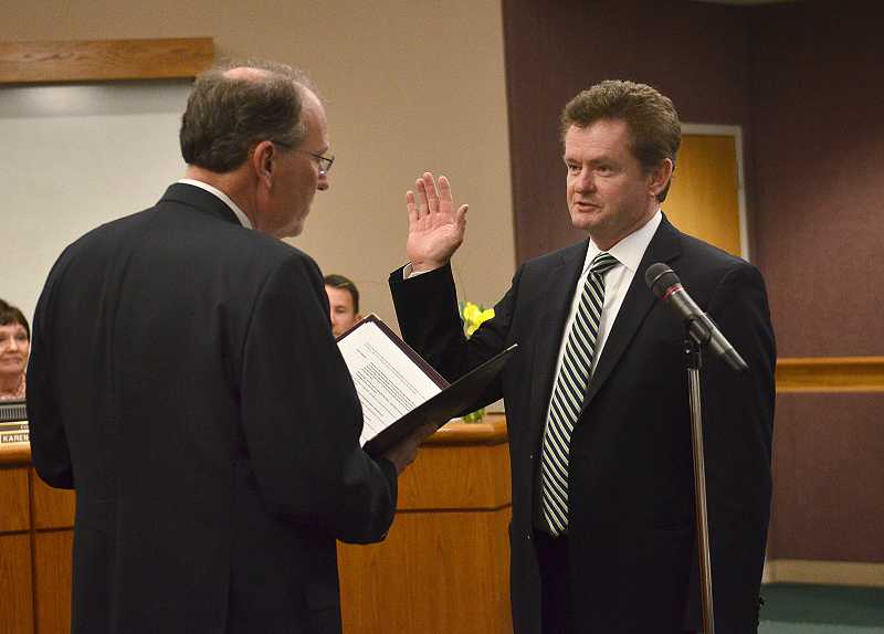by: VERN UYETAKE - Councilor Skip ONeill takes the oath of office Tuesday at city hall.