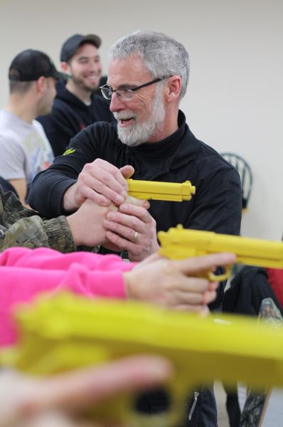 by: SPOTLIGHT PHOTO: KATIE WILSON - Gregg Smith, gun safety instructor and range master at the Clatskanie Rifle and Pistol Club, shows students the proper way to hold and aim a gun using plastic replicas that replicate the weight and feel of real firearms.