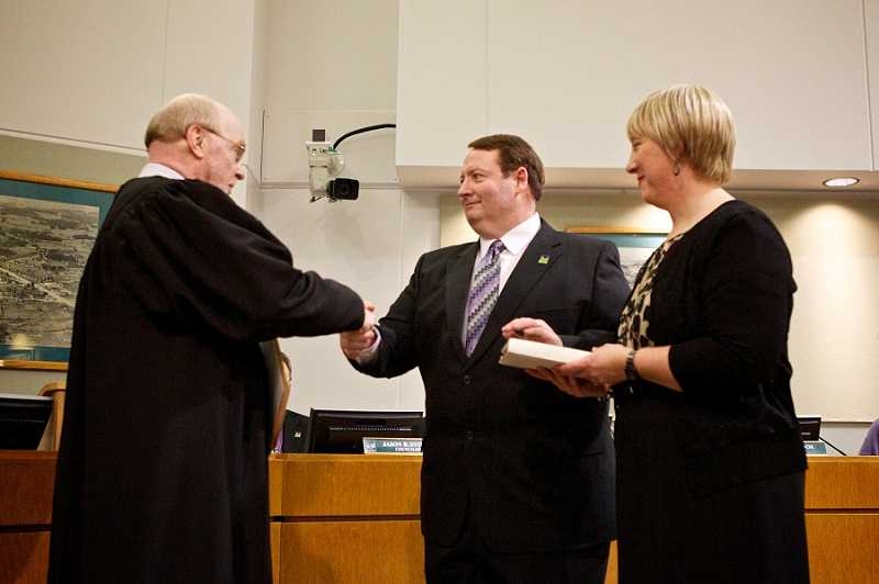 by: JAIME VALDEZ - Tigard Municipal Court Judge Michael O'Brian shakes Tigard Mayor John L. Cook's hand after Cook is sworn in as mayor with his wife, Terri, at his side.