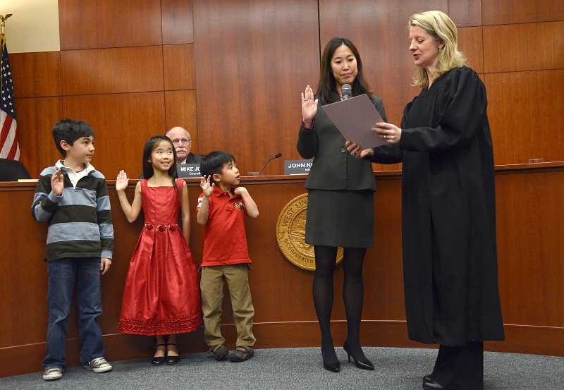 by: VERN UYETAKE - Jenni Tan brought her two children and a friend, from left, fourth-greader Ty Park, Summer Tan, 8, and AJ Tan, 6, as she took her oath of office as a city councilor Monday evening.