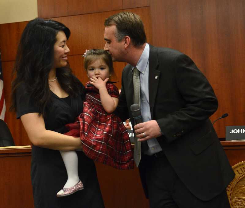 by: VERN UYETAKE -  Thomas Frank kisses his daughter, Aubrey, after being sworn into office. With them is Frank's wife, Jenny.