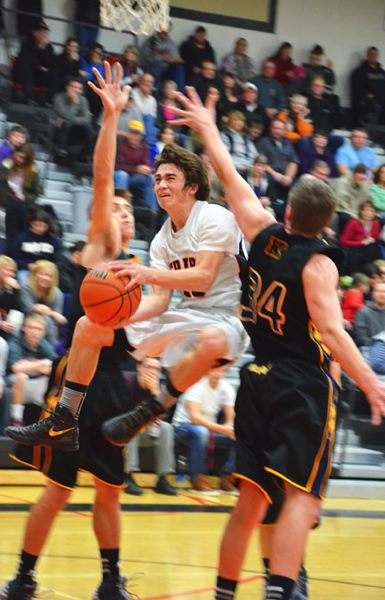 by: JOHN BREWINGTON - Scappoose's Paul Revis splits two posts on his way to the hoop during a recent game.