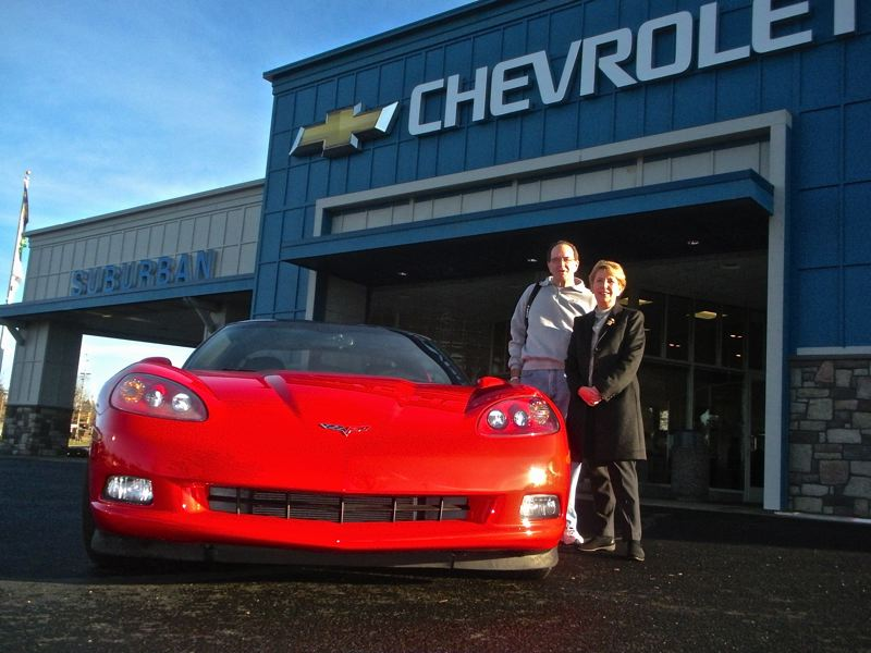 by: POST PHOTO: JIM HART - POST PHOTO: JIM HART  Standing under the new blue arch at the newly remodeled Suburban Chevrolet facility is co-owner of the Suburban Auto Group, Nancy Jaksich, standing alongside the newest owner of one of its many cars, Tim Ferguson of Clackamas. In the photo, Ferguson is ready to drive off the lot with this bright red, showroom-new, 2011 Chevrolet Corvette Coupe.
