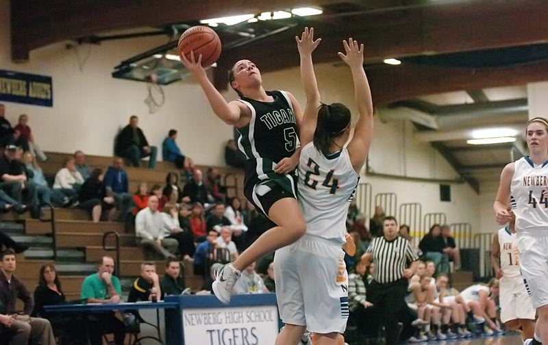 by: DAN BROOD - GLIDING -- Tigard High School junior guard Lexi Carter (5) gets past Newberg's Abbie Woginrich and goes up to the basket in Friday's game.