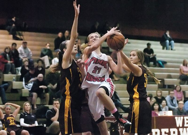 by: DAN BROOD - SPLITTING THE DEFENSE -- Tualatin junior Lindsay Barrow goes to the basket between Forest Grove's Emilia Anderson (left) and Abby Jensen during Tuesday's game. The Wolves got a 55-35 victory.