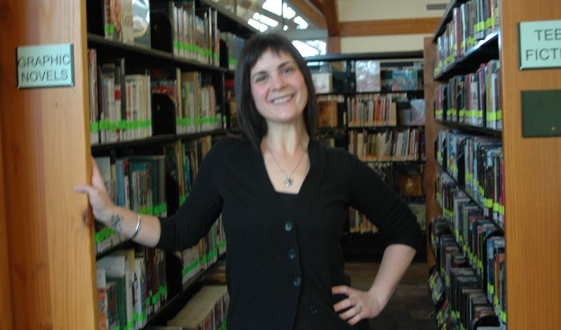 by: NEWS PHOTO: SCOTT JORGENSEN - Estacada's new librarian, Annie Sprague, poses in her favorite section of the facility.
