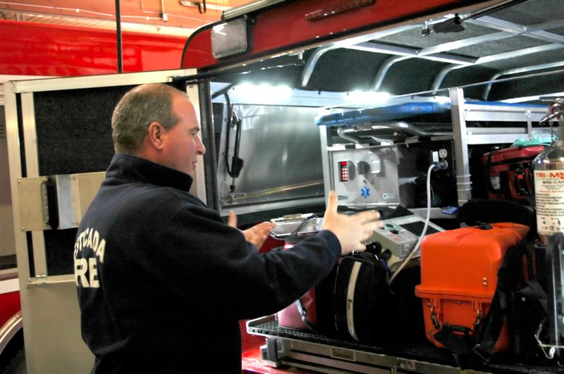 by: NEWS PHOTO: SCOTT JORGENSEN - Lt. Bruce Courtain closes the back of a fire truck after checking equipment.