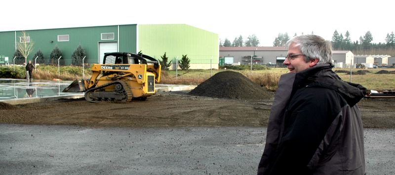 by: NEWS PHOTO: SCOTT JORGENSEN - Northwest Technologies Inc. CEO Eric Sale watches as a crew lays the groundwork for the expansion of its Estacada facility.