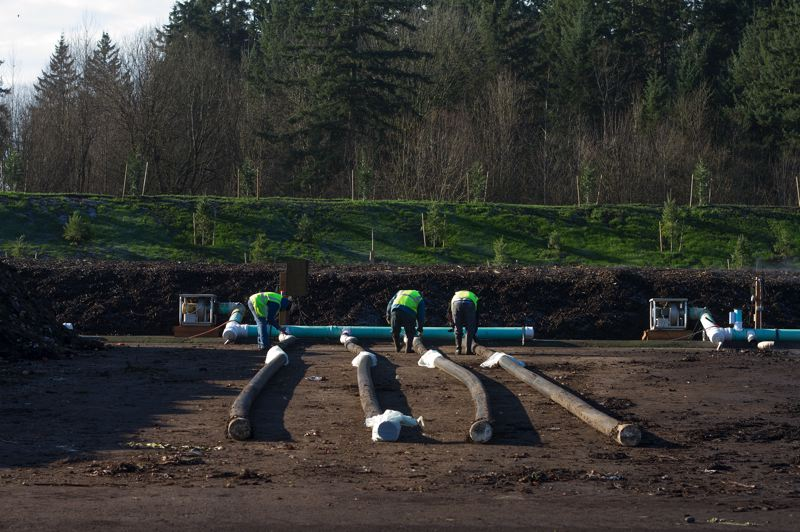 by: HILLSBORO TRIBUNE PHOTO: CHASE ALLGOOD - Workers prepare the air filtration system for a fresh pile of compost.