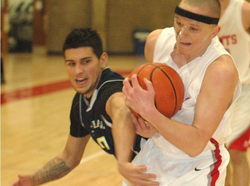 by: THE POST: PARKER LEE - Mt. Hood CC guard Brock Otis protects the ball from a Portland defender on his way to the basket during Wednesdays 13-point win over the Panthers.
