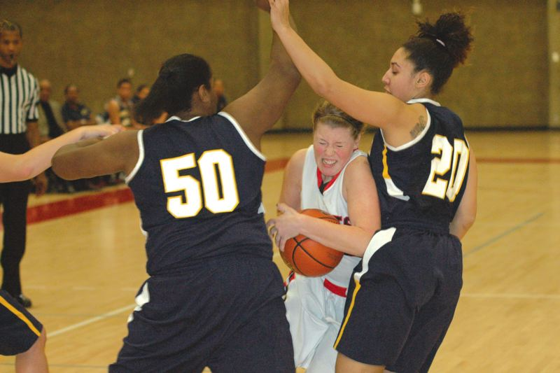 by: THE POST: PARKER LEE - Mt. Hoods Hannah Macoby tries to squeeze between a pair of Portland CC defenders during an 11-point loss to the Panthers on Wednesday - marking eight straight setbacks for the Saints.