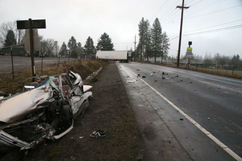 by: PHOTO COURTESY: OREGON STATE POLICE - A seriously injured 25-year-old's Toyota Camry lies crumpled at the side of Carus Road after hitting the semi in the background.