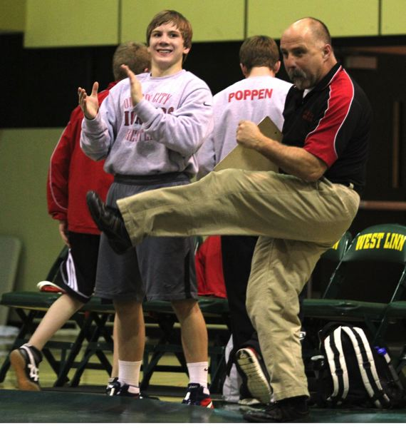 by: JONATHAN HOUSE - Senior Kyle Sether and Oregon City coach Roger Rolen celebrate a fall in last weeks hotly contested Three Rivers League dual meet with cross-river rival West Linn.